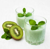 Kiwi smoothie in glass. On a old white wooden background Royalty Free Stock Photography