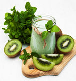 Kiwi smoothie in glass. On a old white wooden background Stock Photography