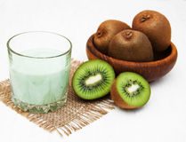 Kiwi smoothie in glass. On a old white wooden background Stock Photos