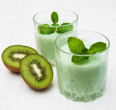 Kiwi smoothie in glass. On a old white wooden background Stock Images