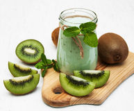 Kiwi smoothie in glass. On a old white wooden background Stock Image