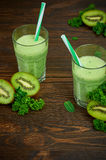 Kiwi smoothie. Healthy kiwi detox in a glass with fresh fruit on a wooden background. Close-up. Selective focus Royalty Free Stock Images