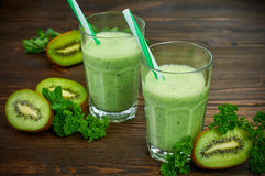 Kiwi smoothie. Healthy kiwi detox in a glass with fresh fruit on a wooden background. Close-up. Selective focus Royalty Free Stock Photo