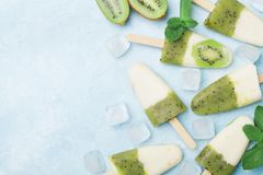 Kiwi smoothie and yogurt fruity popsicles or homemade ice cream top view. Summer refreshing food. stock photos