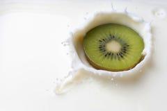 Kiwi som faller in i mjölka med en färgstänk Arkivfoton