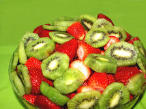 Kiwi and Strawberries. Delicious cut slices of kiwi and strawberries on green background Royalty Free Stock Photos