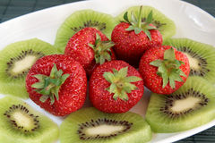 Kiwi and strawberries on a white dish Stock Image