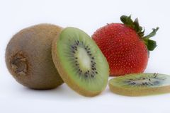 Kiwi and strawberry. Kiwis whole and sliced and a red strawberry Royalty Free Stock Photography