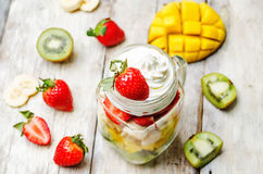 Kiwi strawberry banana mango salad with whipped cream Royalty Free Stock Images