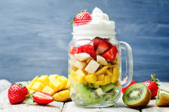 Kiwi strawberry banana mango salad with whipped cream Stock Photos