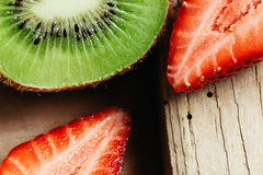 Kiwi and strawberry close up on wood table Stock Photos