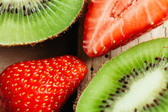 Kiwi and strawberry  macro close up on wood table Royalty Free Stock Photography