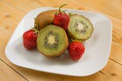 Kiwi with strawberry on plate Stock Photos