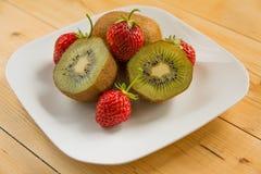 Kiwi with strawberry on plate Royalty Free Stock Photos