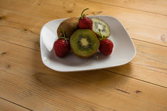 Kiwi with strawberry on plate Stock Image