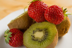 Kiwi with strawberry on plate Royalty Free Stock Photo