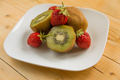 Kiwi with strawberry on plate Royalty Free Stock Photography