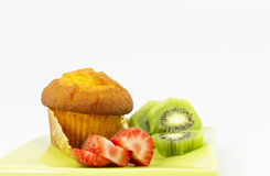 Kiwi and strawberry slices with corn muffin on green plate Royalty Free Stock Photos