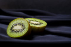 Kiwi sur le tissu noir de satin Image stock