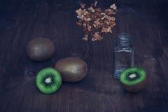 Kiwi sur une table en bois avec un brin des fleurs sèches La vie toujours avec le kiwi Photo libre de droits