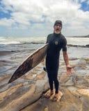Kiwi Surfer local com sua placa, Muriwai, Nova Zelândia imagem de stock royalty free