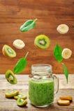 Kiwi szpinaka bananowy smoothie z latanie kawałkami fotografia stock