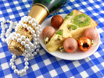 Kiwi tasty cake close up at plate, champagne bottle, diamonds and christmas balls Royalty Free Stock Photo