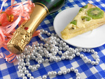 Kiwi tasty cake close up at plate, champagne bottle and flowers Stock Photos