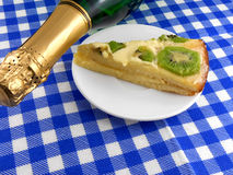 Kiwi tasty cake close up at plate and champagne bottle Stock Images