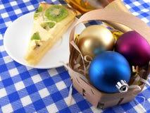 Kiwi tasty cake close up at plate, wine bottle and christmas balls Royalty Free Stock Photos