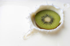 Kiwi tombant dans le lait avec une éclaboussure Photos stock