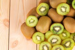 Kiwi in two halves with other kiwis on the back. Wooden background stock image