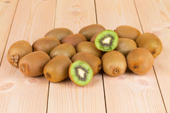 Kiwi in two halves with other kiwis on the back Stock Photos