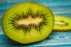 Kiwi and uicy piece of kiwi. Juicy pieces of kiwi on a table, blue table Stock Photo