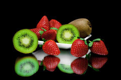 Kiwi und Erdbeeren auf einer Platte auf einem schwarzen Hintergrund mit mirr Lizenzfreie Stockfotografie