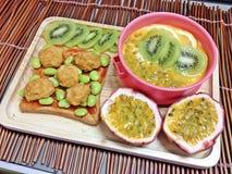 Kiwi- und Maracujajoghurt mit Fischball mischte Tomatensaucespritzen auf den Broten Stockfotos