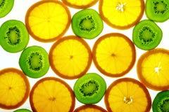 Kiwi vert et parts oranges Photographie stock