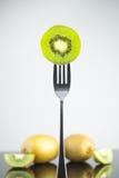 Kiwi vert frais et juteux découpé en tranches sur la fourchette avec le kiwi entier dedans Photographie stock libre de droits