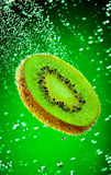 Kiwi in water. Fresh kiwi falls in water on a green background Stock Image
