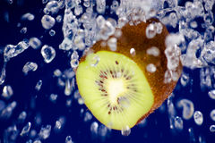 Kiwi in water. On blue Royalty Free Stock Images