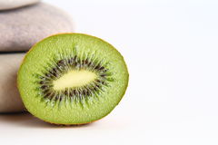 Kiwi on White Background with Stones. Half of a Kiwi on White Background with Stones Stock Images
