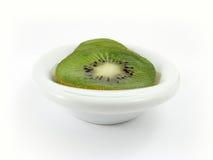 Kiwi on white plate. Kiwi slices on white plate Royalty Free Stock Photography