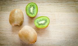 Kiwi on the wooden background: whole fruit and cross section Stock Photo