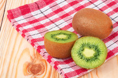 Kiwi on the wooden table. With checkered cloth Royalty Free Stock Image