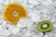 Kiwi y naranja en el hielo Fotos de archivo libres de regalías