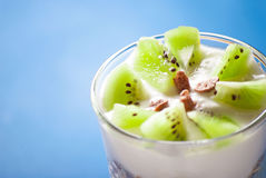 Kiwi and yogurt in glass, close up on blue background Royalty Free Stock Photo