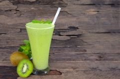Kiwi yogurt smoothies juice,beverage healthy the taste yummy In glass drink episode morning on wood background. Kiwi smoothies colorful green juice beverage royalty free stock photos