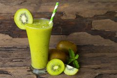 Kiwi yogurt smoothies juice,beverage healthy the taste yummy In glass drink episode morning on wood background. Kiwi smoothies colorful green juice beverage royalty free stock photo
