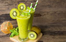 Kiwi yogurt smoothies juice,beverage healthy the taste yummy In glass drink episode morning on wood background. Kiwi smoothies colorful green juice beverage stock photos