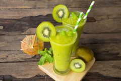 Kiwi yogurt smoothies juice,beverage healthy the taste yummy In glass drink episode morning on wood background. Kiwi smoothies colorful green juice beverage stock photography